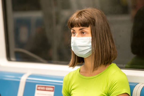 Young woman wearing a face mask protecting against viruses and air pollution taking public transportation stock photo