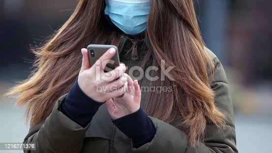 Young woman wearing a face mask using her mobile phone in street