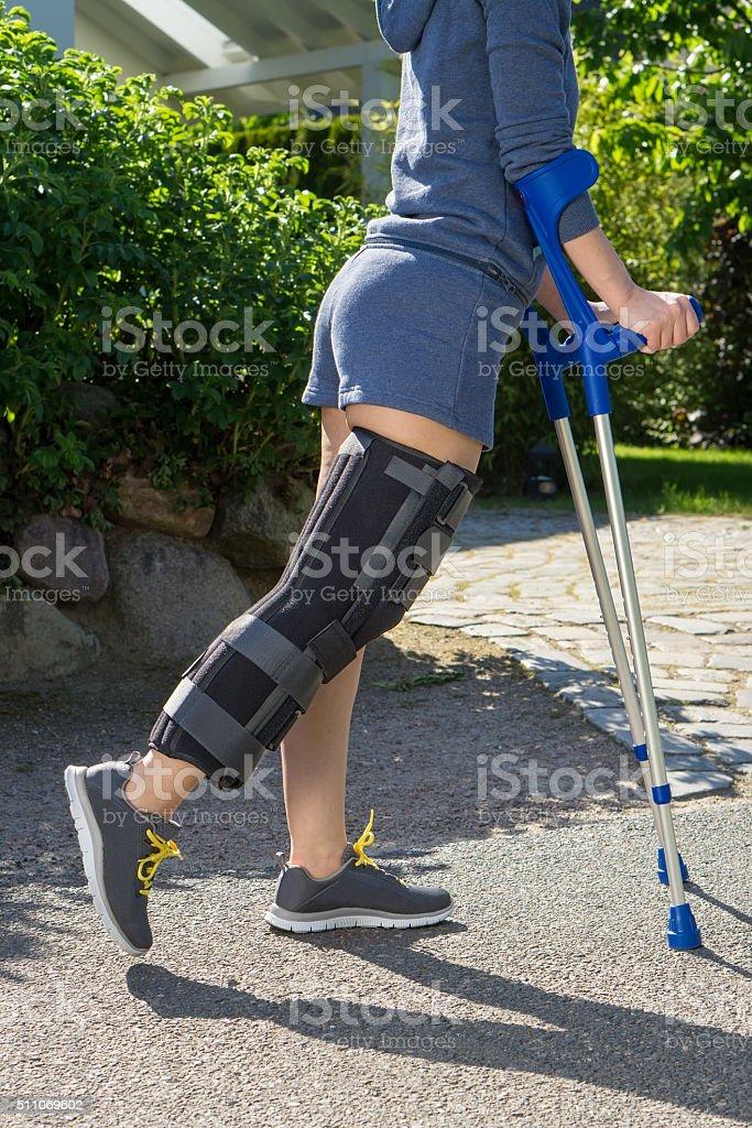 Young woman wearing a leg brace side view. stock photo