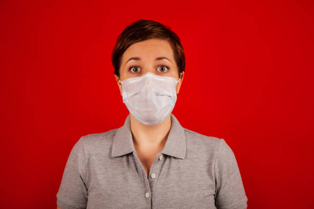 Young woman wearing a medical face mask, studio portrait. Red backdrop. Woman wearing a protective mask. Woman wears a surgical mask for the crown virus stock photo