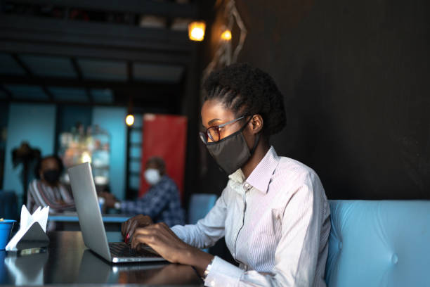 young woman wearing a protective face mask and using a laptop in a restaurant - afro latino mask imagens e fotografias de stock