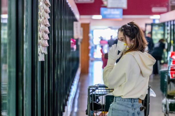 Eine junge Frau, die in einer Zeit der Viruspandemie eine Schutzmaske und Handschuhe trägt und lebensmittelaufbereitet - verarbeitete Tiefkühlkost - kauft. – Foto
