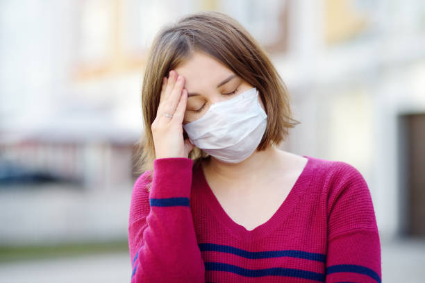 Young woman wearing a protective mask in public place. Safety during COVID-19 outbreak. stock photo