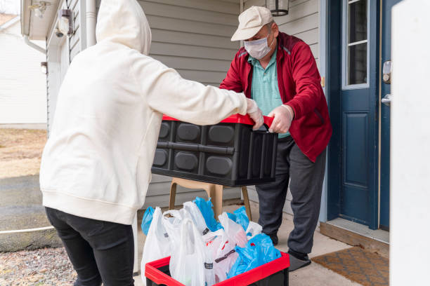 young woman wearing a protective n95 mask, a courier, is handing the groceries packed into reusable plastic bins to a customer, a senior man, on the porch of his house during covid-19 outbreak. - servizi essenziali foto e immagini stock