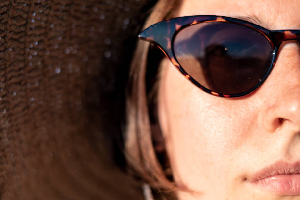 Young woman wearing a summer hat and sunglasses, close-up portrait. Summer vacation, sunny weather, holiday mood concept - young girl's head with freckles in retro eyeglasses dark spots face stock pictures, royalty-free photos & images