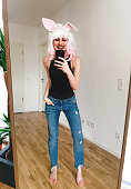 Young woman wearing a wig taking selfies in a mirror
