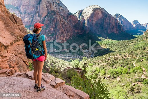Young woman wearing backpack is looking at the view on the trail to Angel's Landing in Zion National park in Utah, USA. Female on a hiking trail in Zion National Park in Usa.