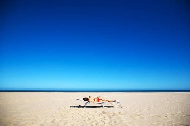 Young Woman Wearing Bikini and Lying on Beach Chair stock photo