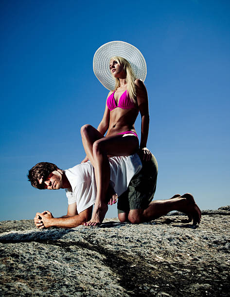 young woman wearing bikini and sitting on man's back - man dominating woman stock photos and pictures