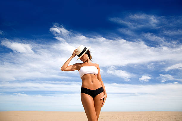 young woman wearing bikini and standing on beach - beautiful curvy girls stock photos and pictures