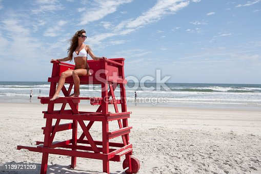 Young woman in bikini sitting atop a lifeguard stand on the beach with blue sky background.
