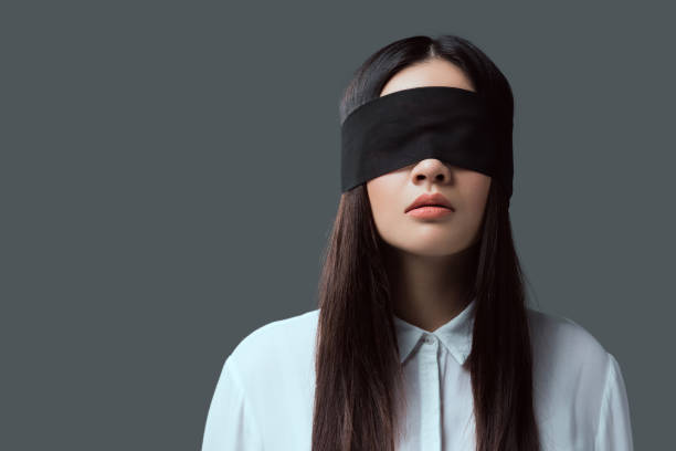 young woman wearing black blindfold isolated on grey stock photo