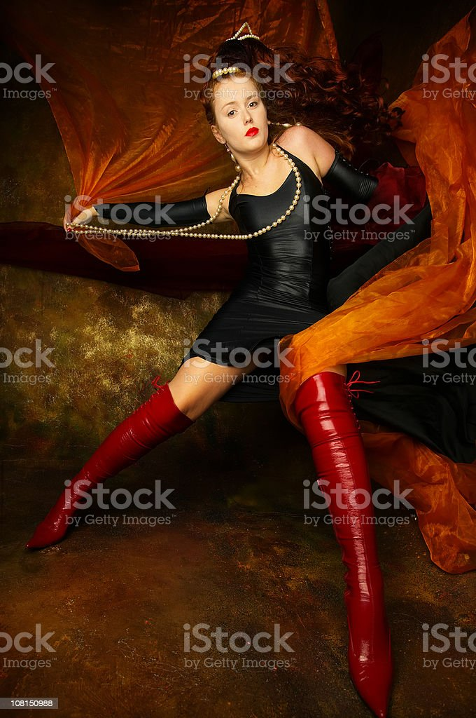 Young Woman Wearing Black Dress and Posing with Orange Silk royalty-free stock photo