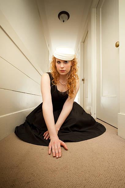 Jovem mulher usando vestido preto posando em um corredor de vazio - foto de acervo