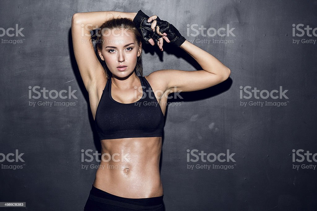 Young woman wearing black sports bra and gloves stock photo