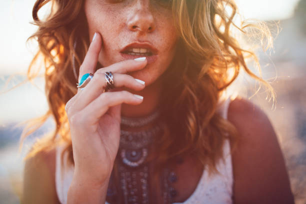 Young woman wearing bohemian style silver jewelry Close-up of bohemian woman with freckles wearing boho style silver turquoise rings and necklaces romani people stock pictures, royalty-free photos & images
