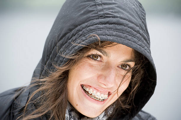 young woman wearing braces, outdoor portrait on a rainy day stock photo