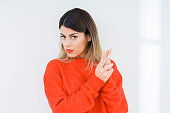 Young woman wearing casual red sweater over isolated background Holding symbolic gun with hand gesture, playing killing shooting weapons, angry face