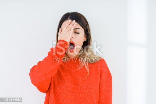 Young woman wearing casual red sweater over isolated background Yawning tired covering half face, eye and mouth with hand. Face hurts in pain.