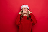 Young woman wearing christmas hat smiling happy pointing with hand and finger on herself isolated on red background