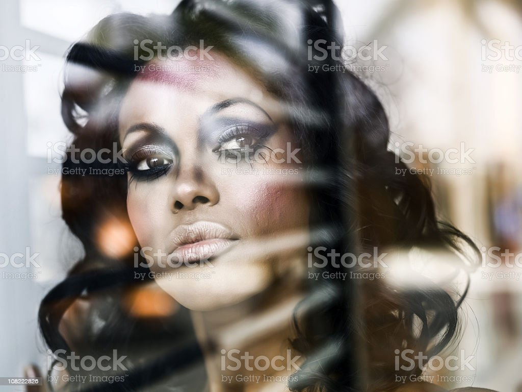 young woman wearing dark make-up looking through window royalty-free stock photo