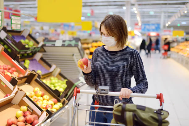 young woman wearing disposable medical mask shopping in supermarket during coronavirus pneumonia outbreak - shopping стоковые фото и изображения
