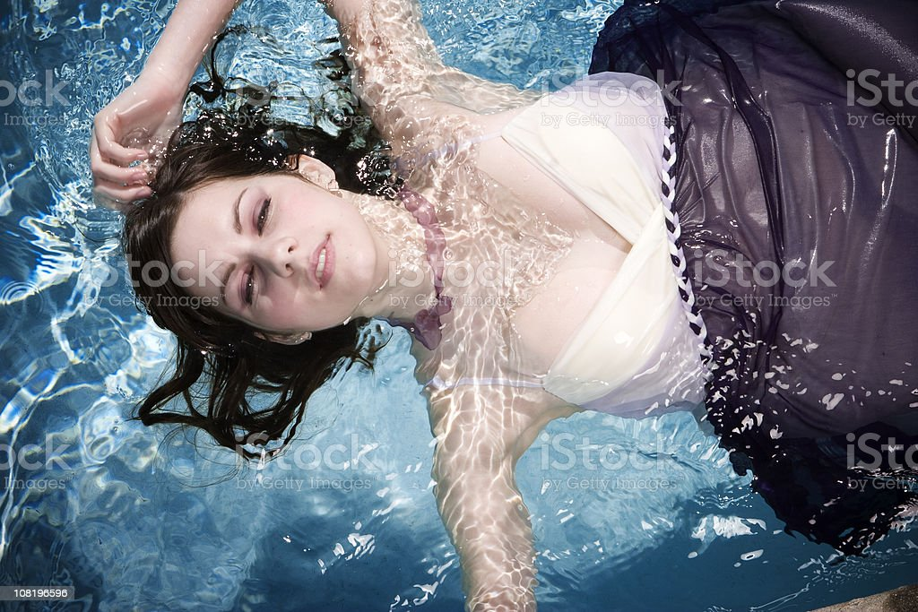 Young Woman Wearing Dress and Floating in Water royalty-free stock photo