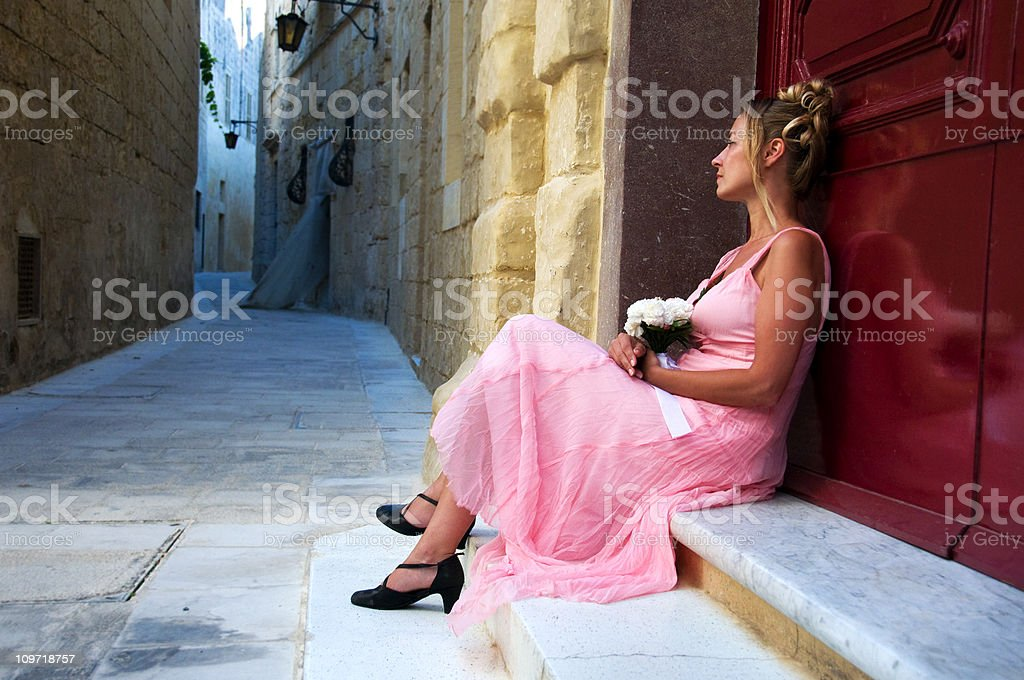 Young Woman Wearing Dress and Waiting Outside stock photo
