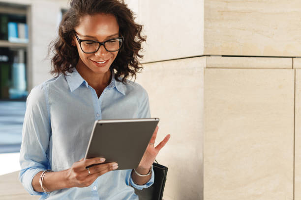 Young woman wearing eyeglasses reading and browsing on digital tablet stock photo