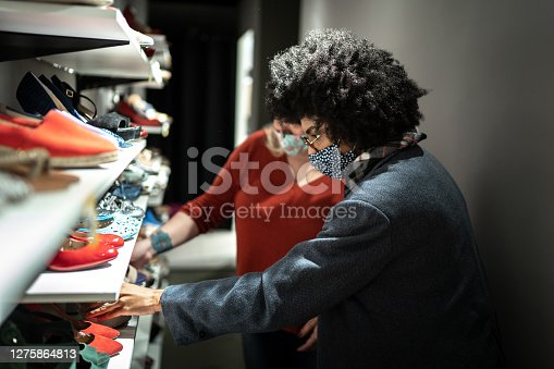 Young woman wearing face mask being helped by a saleswoman while shopping for shoes in a thrift store