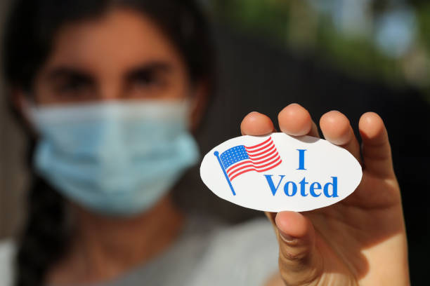 Young woman wearing face mask holding I Voted sticker stock photo