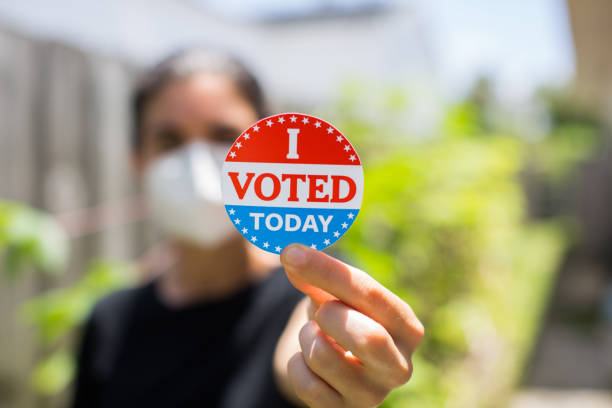 Young woman wearing face mask holding I voted today sticker stock photo