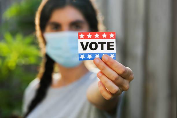 mujer joven que lleva máscara facial sosteniendo la etiqueta engomada del voto - voting fotografías e imágenes de stock