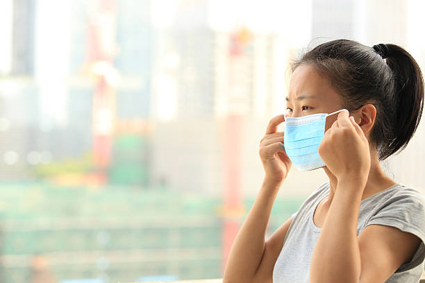 young woman wearing face mask on city stock photo