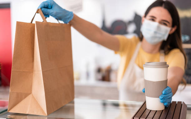 Young woman wearing face mask while serving takeaway breakfast and coffee inside cafeteria restaurant - Worker preparing delivery food inside bakery bar during coronavirus period - Focus on right hand stock photo