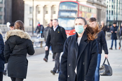 istock Young woman wearing face mask while walking in the streets of London 1210333449