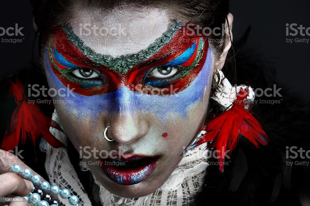 Young Woman Wearing Face Paint Make-Up and Feather Earrings royalty-free stock photo