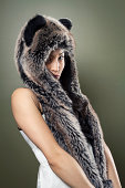 A shy young Chinese woman wearing a fur animal hat.