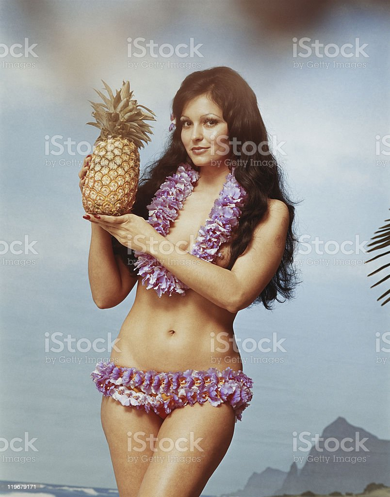 Young woman wearing garland holding pineapple, smiling, portrait royalty-free stock photo