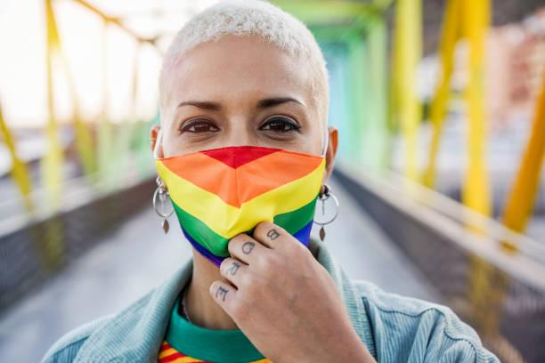 ゲイプライドマスクを身に着けている若い女性 - lgbtの権利、多様性、寛容と性同一性の概念 - lgbtqi  ストックフォトと画像