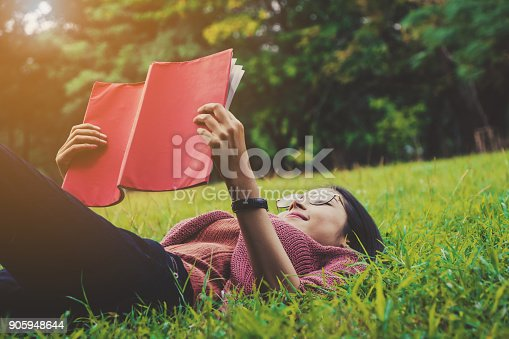istock Young woman wearing glasses enjoy reading a red book lying on green grass 905948644