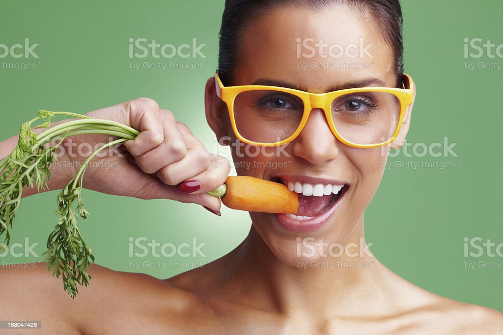 Young woman wearing glasses while eating fresh carrot stock photo