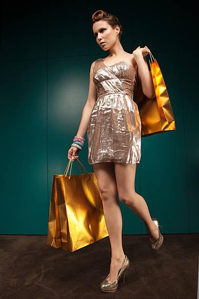 junge frau in gold-kleid mit einkaufstüten, porträt - schuhe auf englisch stock-fotos und bilder