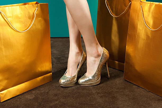 junge frau mit goldenen stilettos mit einkaufstaschen - schuhe auf englisch stock-fotos und bilder