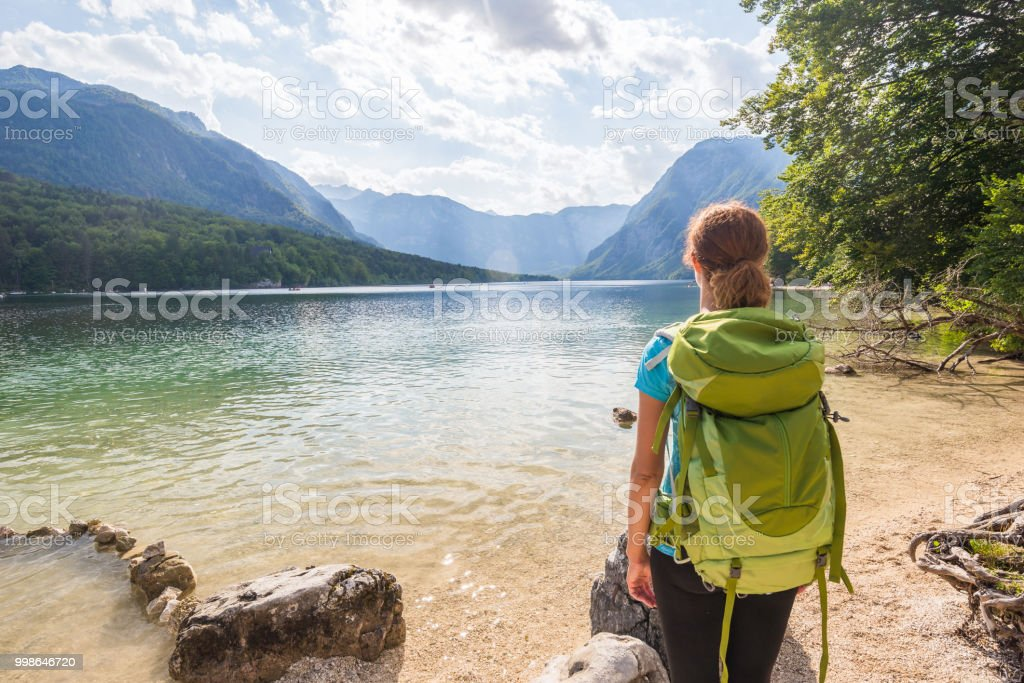 Young woman wearing green backpack is standing by the Bohinj lake in Bohinj, Slovenia stock photo