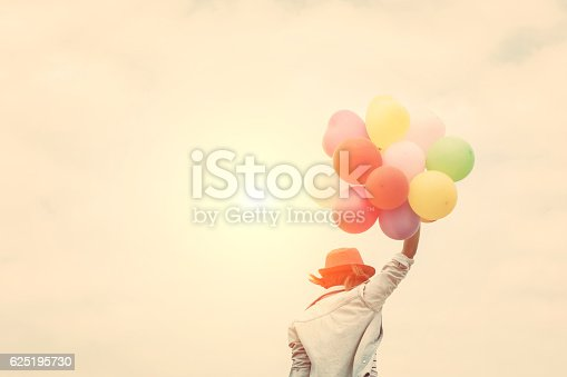 istock Young woman wearing hat holding colorful of balloon 625195730