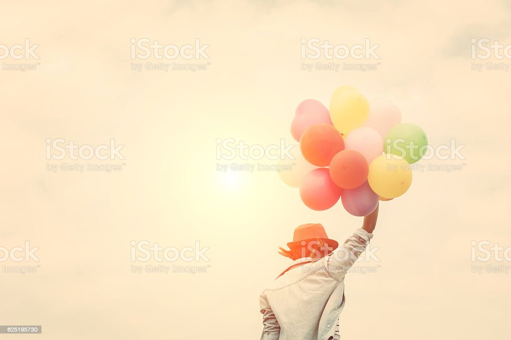 Young woman wearing hat holding colorful of balloon - foto de stock