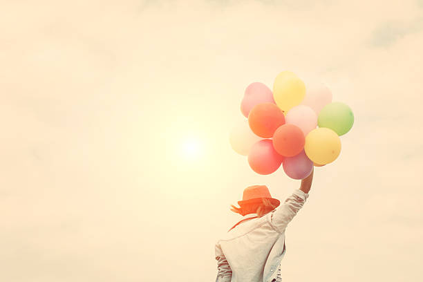 Young woman wearing hat holding colorful of balloon stock photo