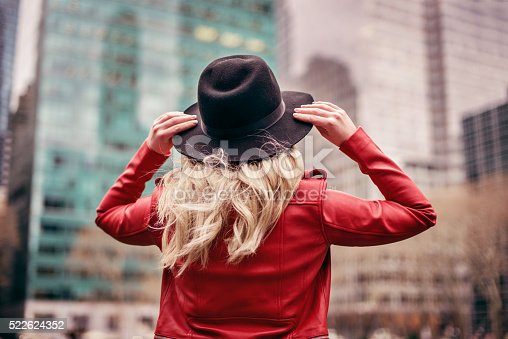 istock young woman wearing hat walking on streets of New York 522624352