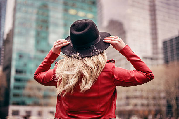 young woman wearing hat walking on streets of New York stock photo